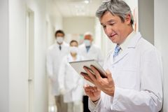 Doctor Holding Digital Tablet. Mature male doctor using digital tablet with colleagues walking in background Stock Photography