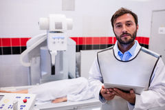 Doctor holding digital tablet and patient lying on x ray machine Royalty Free Stock Image
