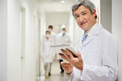 Doctor Holding Digital Tablet. Portrait of mature male doctor holding digital tablet with colleagues walking in background Stock Image