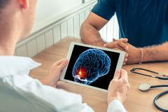 Doctor holding a digital tablet with x-ray of 3D brain of the patient with pain on the front. Cancer headache or trauma concept. Doctor holding a digital tablet stock photography