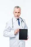Doctor holding digital tablet. Serious male doctor holding digital tablet and looking at camera Royalty Free Stock Photography