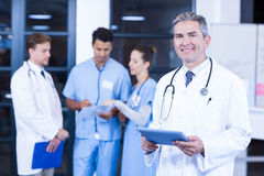 Doctor holding digital tablet and smiling at camera Royalty Free Stock Photos