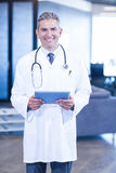 Doctor holding digital tablet and smiling at camera Royalty Free Stock Image