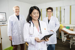 Doctor Holding Digital Tablet While Standing With Colleagues Stock Photo