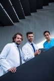 Doctor holding digital tablet standing on staircase with colleagues Stock Photos