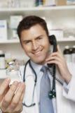 Doctor Holding Drug Bottle While Using Telephone Stock Photo
