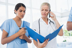Doctor holding folder and having phone call Royalty Free Stock Images