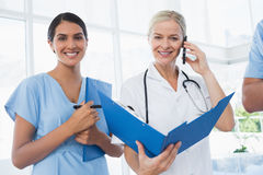 Doctor holding folder and having phone call Stock Image