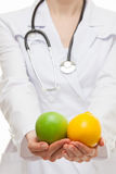 Doctor holding fresh fruits Royalty Free Stock Images