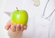 Doctor holding a fresh green apple. White background Royalty Free Stock Photography