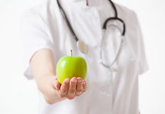 Doctor holding a fresh green apple. White background Royalty Free Stock Photo