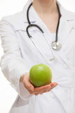 Doctor holding a fresh green apple. White background Royalty Free Stock Images