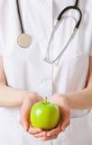 Doctor holding fresh green apples stock photos