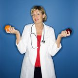 Doctor holding fruit. Royalty Free Stock Photo