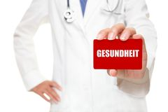 Doctor holding GESUNDHEIT card in german Stock Photos