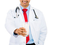 Doctor holding glass of milk in front of chest, good for osteoporosis and bone health. Closeup portrait of doctor holding glass of milk in front of chest, good royalty free stock image