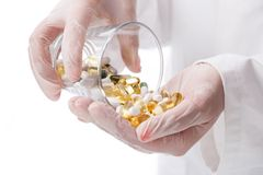 Doctor holding glass of pills Royalty Free Stock Photo