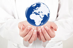 Doctor holding globe on her hands Royalty Free Stock Images
