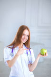 Doctor holding a green apple. Concept of healthy food. Royalty Free Stock Photos