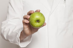 Doctor holding a green apple Stock Images