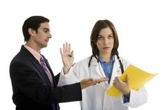 Doctor holding hand up with businessman trying to talk Royalty Free Stock Photo