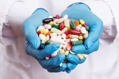 Doctor holding handful of pills royalty free stock photo