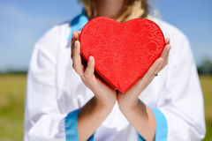 Doctor holding hands with heart, close up picture Stock Photos