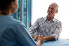 Doctor holding hands of senior man while consoling at table Stock Image
