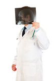 Doctor holding heads roentgen in front of his head Royalty Free Stock Images