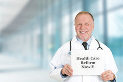 Doctor holding health care reform now sign standing in hospital. Senior happy doctor holding health care reform now sign standing in hospital hallway background Royalty Free Stock Photos