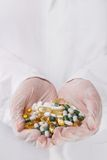 Doctor holding heap of pills Stock Images