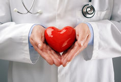 Doctor holding heart with care Stock Photo