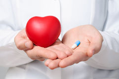 Doctor holding a heart and a pill. Female doctor showing a red heart and a blue pill Stock Photos