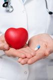 Doctor holding a heart and a pill Stock Image
