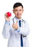Doctor holding heart shape toy and thumb up Royalty Free Stock Images
