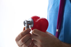 Doctor holding a heart and  stethoscope on  white background Royalty Free Stock Photos