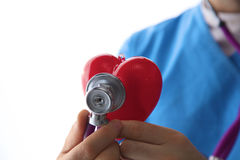 Doctor holding a heart and stethoscope on white background royalty free stock photo