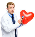 Doctor holding heart on white background. Attractive young doctor holding red heart balloon Stock Photography