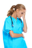 Doctor holding her head in anguish. Attractive young female nurse or doctor dressed in scrubs with a stethoscope holding her hand to her head in anguish stock images