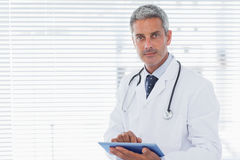 Doctor holding his tablet pc and looking at camera Stock Images