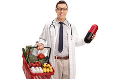 Doctor holding a huge pill and groceries Royalty Free Stock Image
