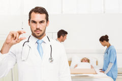 Doctor holding injection with colleagues and patient behind Stock Photo