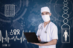 Doctor holding laptop on digital background Stock Image