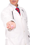 Doctor holding a lot of colorful pills Stock Photography