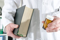 Doctor holding a medical book and a bottle of pills Stock Photo