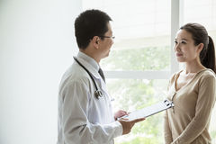 Doctor holding medical charts and discussing with a female patient in the hospital Stock Image