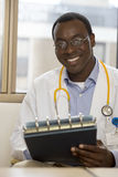 Doctor holding medical file, smiling, front view, portrait Stock Photos