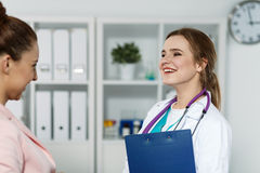 Doctor holding medical history while chatting with patient Royalty Free Stock Photos
