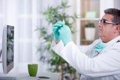 Doctor holding medical injection syringe Stock Image