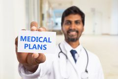 Doctor holding medical plans card in hand. Indian male doctor holding medical plans text white card in hand with trustworthy expression stock image